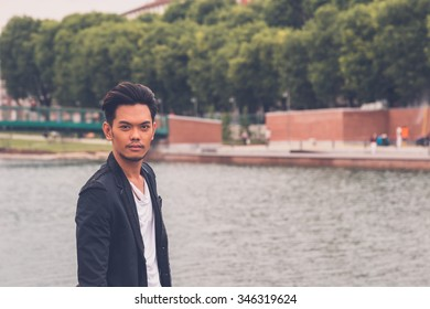 Young handsome Asian model dressed in black posing by an urban artificial basin