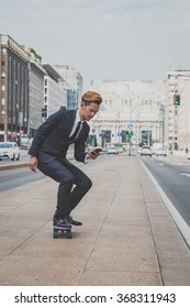 Young handsome Asian model dressed in dark suit and tie riding his skateboard while texting