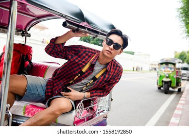 Young handsome Asian tourist man riding local TukTuk taxi while solo traveling in Bangkok city Thailand