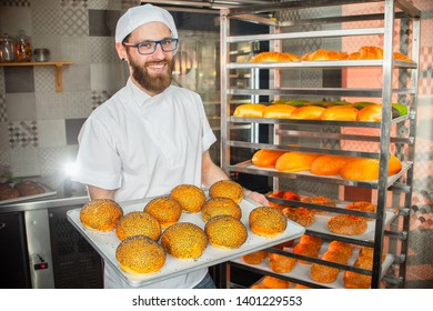 A young handsome baker holding fresh buns with poppy seeds in the background of the oven.