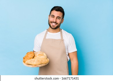 Young handsome baker man isolated happy, smiling and cheerful.