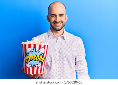 Young handsome bald man holding popcorn looking positive and happy standing and smiling with a confident smile showing teeth