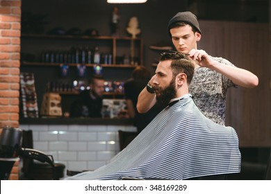 Young handsome barber making haircut of attractive bearded man in barbershop