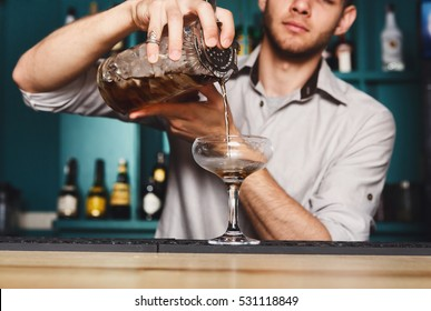 Young handsome Barman in bar interior mixing alcohol cocktail. Professional bartender at work in bar pouring sweet drink into glass on party at night club