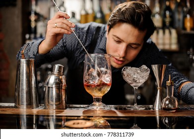 Young and handsome barman stirring fresh alcoholic cocktail with sweet fruit syrups on the bar counter