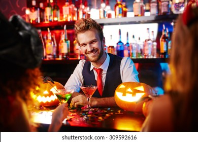 Young handsome bartender working at Halloween