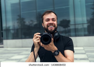 Young handsome beard man in white shirt and trousers makes beautiful pictures on film retro camera, stylishly dressed, photographer,outdoor portrait, close up,brutal, tattoo, street photo,photographer