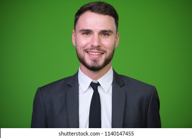 Young handsome bearded businessman against green background