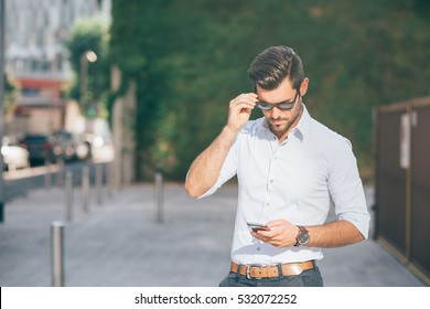 young handsome bearded businessman holding a smart phone, looking down tapping screen - technology, business, work concept