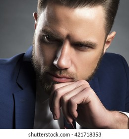 Young handsome bearded caucasian man with blue eyes sitting on chair. Perfect skin and hairstyle. Wearing blue suit and tie. Studio portrait on gradient black to grey background. Toned