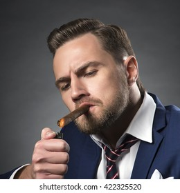 Young handsome bearded caucasian man sitting on chair with cognac and fire a cigar. Perfect skin and hairstyle. Wearing blue suit. Studio portrait on gradient black to grey background. Toned