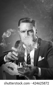 Young handsome bearded caucasian man sitting on chair with cognac and a cigar. Perfect skin and hairstyle. Wearing suit and watch. Studio portrait on gradient black to grey background. Black and white