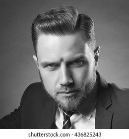 Young handsome bearded caucasian man with blue eyes sitting on chair. Perfect skin and hairstyle. Wearing suit. Studio portrait on gradient black to grey background. Black and white