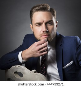 Young handsome bearded caucasian man with blue eyes sitting on chair. Perfect skin and hairstyle. Wearing blue suit and tie. Studio portrait on gradient black to grey background.