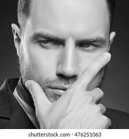 Young handsome bearded caucasian man with blue eyes. Perfect skin and hairstyle. Wearing blue suit. Studio portrait on gradient black to grey background. Black and white