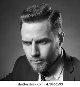 Young handsome bearded caucasian man with blue eyes sitting on chair. Perfect skin and hairstyle. Wearing blue suit. Studio portrait on gradient black to grey background. Black and white