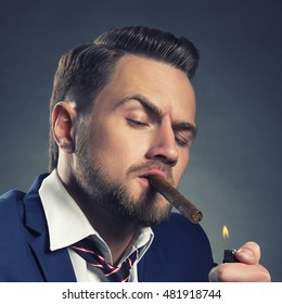 Young handsome bearded caucasian man sitting on chair with cognac and a cigar. Perfect skin and hairstyle. Wearing blue suit and watch. Studio portrait on gradient black to grey background.