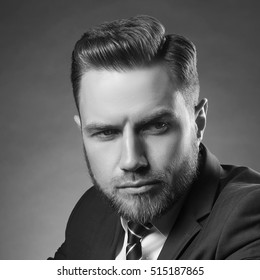 Young handsome bearded caucasian man with blue eyes sitting on chair. Perfect skin and hairstyle. Wearing blue suit and tie. Studio portrait on gradient black to grey background. Black and white