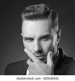 Young handsome bearded caucasian man with blue eyes. Perfect skin and hairstyle. Wearing blue suit and watch. Studio portrait on gradient black to grey background. Black and white