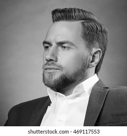 Young handsome bearded caucasian. Perfect skin and hairstyle. Wearing grey suit. Studio portrait on gradient black to grey background. Black and white