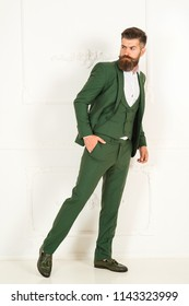Young handsome bearded gentleman in fashion green suit white shirt and green male shoes in studio. Hipster with stylish appearance in luxury place. Man with beard and mustache. Stylish hipster concept