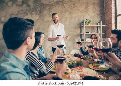 Young handsome bearded guy is talking and smiling. Friends are celebrating with tasty dishes and drinks, enjoying themselves
