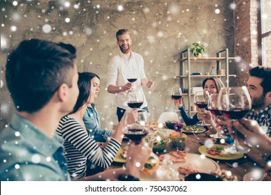 Young handsome bearded guy is talking and smiling. Friends are celebrating with tasty dishes and drinks, enjoying themselves, enjoying winter vacation, snowfall xmas background