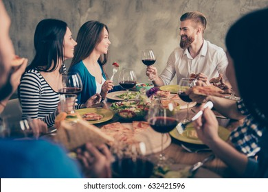 Young handsome bearded guy is telling the toast to a brunette cute girl, a birthday girl. Friends are celebrating with tasty dishes and drinks, smiling and enjoying themselves