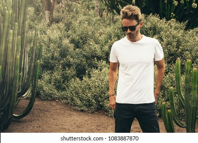 Young handsome bearded guy wearing a blank white t-shirt and sunglasses is standing in the garden background next to a big cactus plant. Horizontal mock up style