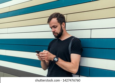 young handsome bearded hipster man using smartphone and listening music with earphones in the city, headphones, sunglasses street, outdoor portrait, cap, hat, concept, hipster male, wall