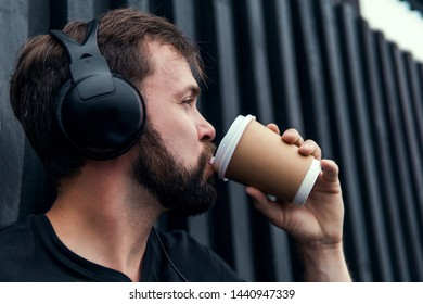 young handsome bearded hipster man using smartphone and listening music with earphones in the city, headphones, sunglasses street, outdoor portrait, cap, hat, concept, hipster male, wall, coffee cup