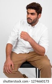 Young handsome bearded Indian man thinking and sitting on chair