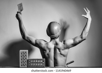 young handsome bearded macho man builder with sexy muscular athletic strong body. has strong hands and back in orange hard hat or helmet posing with brick and tool.