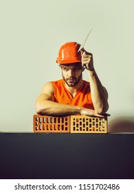 young handsome bearded macho man builder with sexy muscular athletic strong body has strong hands in orange uniform and hard hat or helmet holds tool and lean on brick, copy space