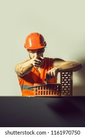 young handsome bearded macho man builder with sexy muscular athletic strong body has strong hands in orange uniform and hard hat or helmet with brick and tool, copy space
