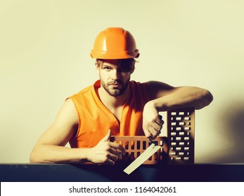 young handsome bearded macho man builder with sexy muscular athletic strong body has strong hands in orange uniform and hard hat or helmet with brick and tool.