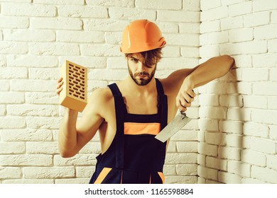 young handsome bearded macho man builder with sexy muscular athletic strong body has strong hands in blue uniform and orange hard hat or helmet holds brick and tool on white brick wall background.