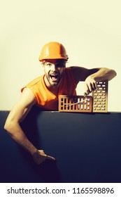 young handsome bearded macho man screaming builder with sexy muscular athletic strong body has strong hands in orange uniform and hard hat or helmet with brick and tool.