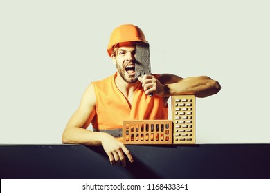 young handsome bearded macho man screaming builder with sexy muscular athletic strong body has strong hands in orange uniform and hard hat or helmet with bricks and tool.