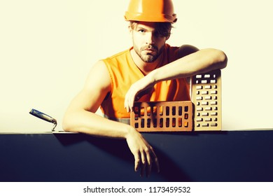 young handsome bearded macho man builder with sexy muscular athletic strong body has strong hands in orange uniform and hard hat or helmet with brick and tool isolated on white, copy space