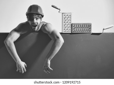 young handsome bearded macho man screaming builder with sexy muscular athletic strong body has strong hands in orange hard hat or helmet with brick and tool, copy space