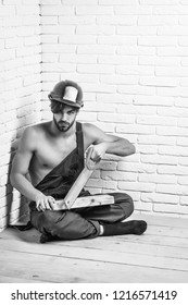 young handsome bearded macho man builder with sexy muscular athletic strong body has strong hands in blue uniform and orange hard hat or helmet holds wood and saw on white brick wall background.