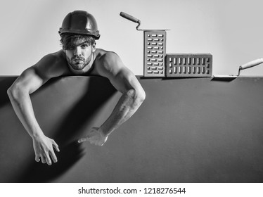 young handsome bearded macho man tired builder with sexy muscular athletic strong body has strong hands in orange hard hat or helmet with brick and tool, copy space