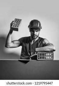 young handsome bearded macho man builder with sexy muscular athletic strong body has strong hands in orange uniform and hard hat or helmet holds brick and tool, copy space