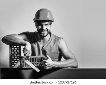 young handsome bearded macho man smiling builder with sexy muscular athletic strong body has strong hands in orange uniform and hard hat or helmet with brick and tool, copy space