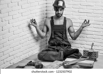 young handsome bearded macho man builder with sexy muscular athletic strong body has strong hands in blue uniform and orange hard hat or helmet with wood axe drill and saw on white brick wall.