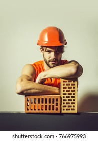 young handsome bearded macho man builder with sexy muscular athletic strong body has strong hands in orange uniform and hard hat or helmet lean on brick