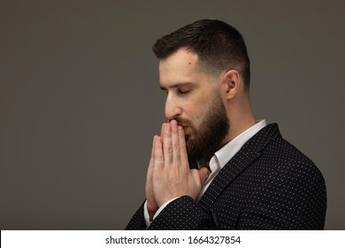 Young handsome bearded man against a grey background holding hands in pray near mouth, feels confident.