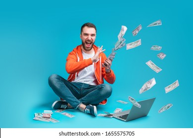 Young handsome bearded man celebrating victory after betting at bookmaker's website throwing dollar banknotes with happy excited face expression. Lucky winner hit a jackpot in online lottery.