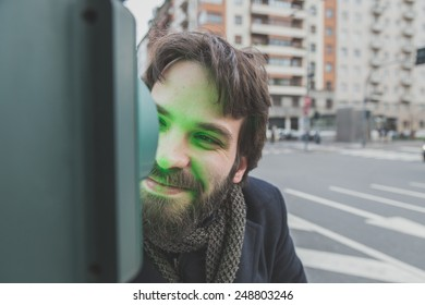 Young handsome bearded man with coat posing in the city streets